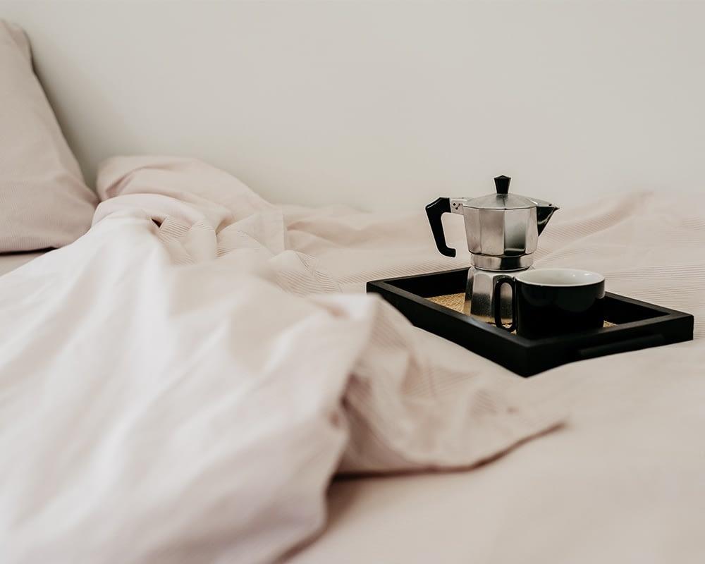 opgemaakt bed met roze-wit gestreept beddengoed