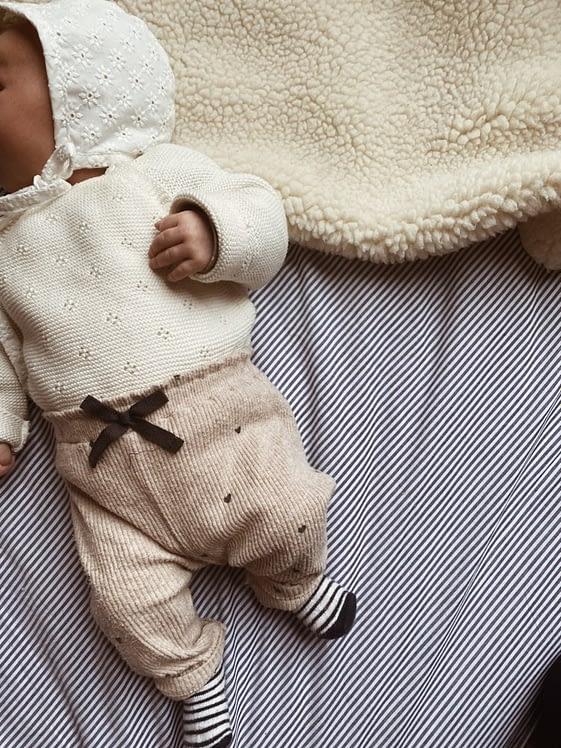 slapende baby op gestreept beddengoed