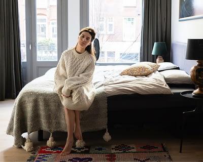 vrouw op bed in grote en lichte slaapkamer